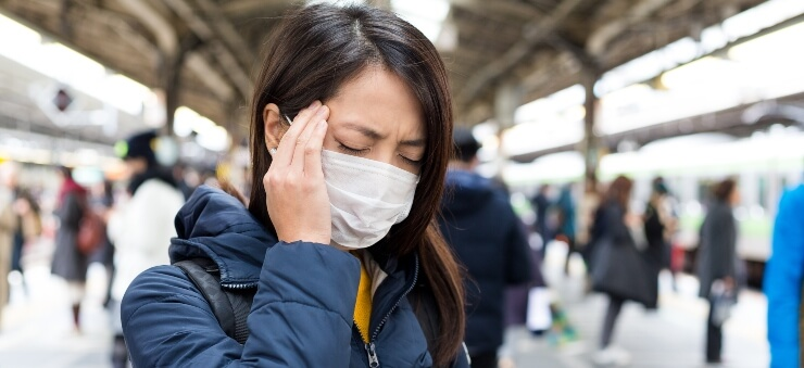 Chinese woman wearing mask indicates she is unwell