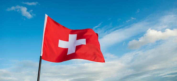 Swiss flag waving against the sky