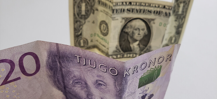 kronor money note in front of a dollar bill